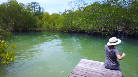 intertidal : Video of Asian girl wearing hat sits on a small pier next to the Intertidal forest