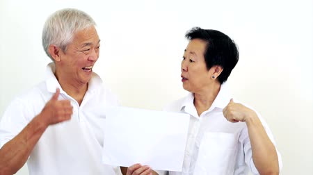 good : Asian senior couple look at the white sign together. Surprise and happy with the deal on blank white sign Stock Footage