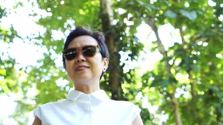 eski moda : Cool Asian senior woman wearing sunglasses in green natural background on  white shirt