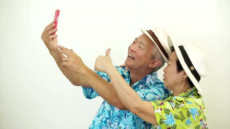Asian senior tourist couple taking a selfie on holiday vacation