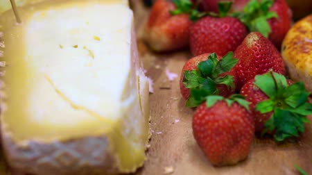гауда : cheese with strawberry, berries and fruits on wood platter Стоковые видеозаписи