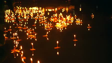yansıma : Loi Krathong Festival in Chiangmai, Thailand. Hand releasing floating decorated baskets and candles to pay respect to river goddess. Thai traditional culture on full moon night