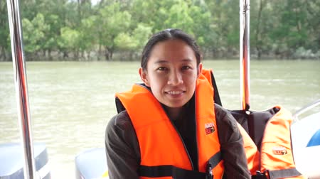 cheated : Ranong, Thailand - October 2015: Asian woman smiling wearing life vest jacket for safety on the boat trip