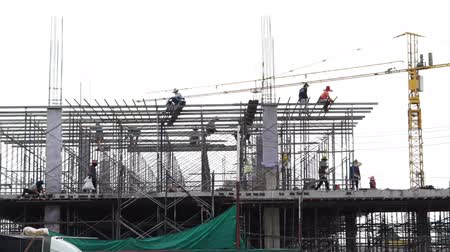 planos : construction and development. Workers working on new building with crane in background Stock Footage