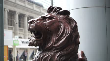 pinturas : Hong Kong - April 2016:Wet lion statue at the entrance of HSBC Bank head quarter Tower in Central District, Hong Kong in the rainy day