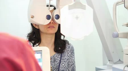 sighted : Asian woman having her eyes sight examined checked by doctor, Optometry concept Stock Footage