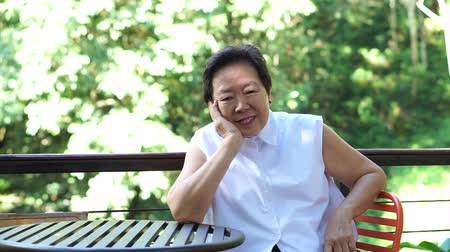 düşünceli : Beautiful senior Asian woman relax sitting thinking with green nature background Stok Video