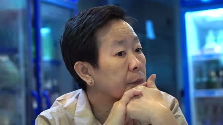 expressão facial : video of Asian senior woman sitting and wait in restaurant