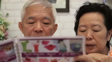 обедающий : Asian senior couple looking at menus in a restaurant together