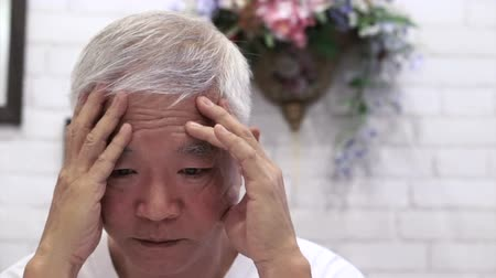 mężczyźni : video of Asian senior guy with hand on face thinking, worry and sad