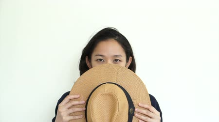 скрывать : Asian girl with hat hiding face and smile