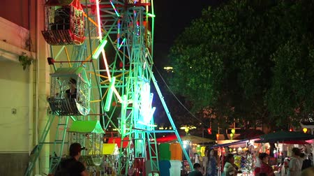 yeepeng : Chiangmai, Thailand - November 2015:  Night temple market at Loi krattong festival. Lot of street food vendor stalls, game and ferris wheel. Local and tourist enjoying night attractions Stock Footage