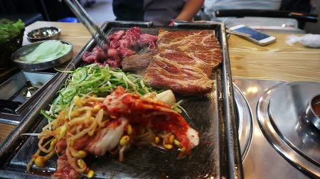 korejština : Traditional Korean barbecue and side dishes vegetable food. Grilled on big stone plate