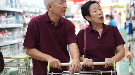 tajlandia : asian senior couple shopping at supermarket with cart