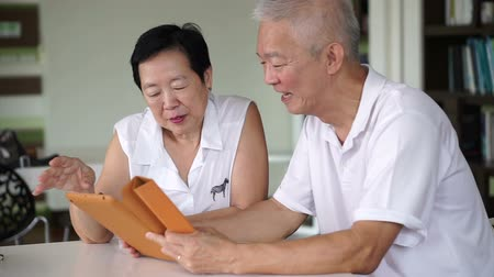 idősek : Asian senior couple reading news together from tablet in small library. Learning and study concept