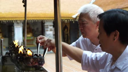 ábrázol : Asian senior doing Buddhist ritual pouring oil to fill candle frame for BUddha statue Stock mozgókép