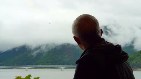tek başına : Asian senior man sitting alone and look out to mountain and lake view