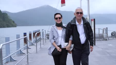 cidadão idoso : Stylish Asian senior walking together at lake cruise ship pier. Traveling around the world together