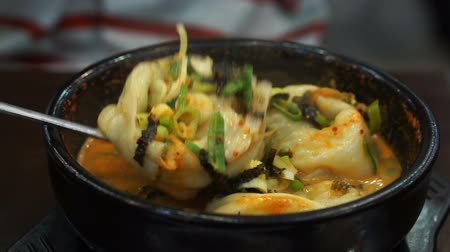won ton : Spoon taking dumpling from Korean spicy stew serve in hot pot Stock Footage