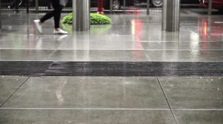 hong kong foot : silhouette of Asian pedestrians in business area walking on rainy building pavement