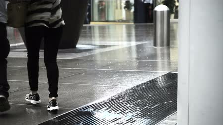 hong kong foot : Asian pedestrians walking through rain in business district area on wet floor Stock Footage