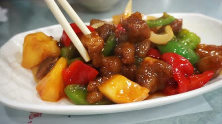 savanyú : Chopsticks eating sweet and sour pork in Hong Kong restaurant, Chinese cuisine Stock mozgókép