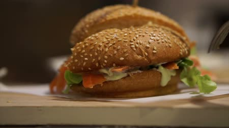 bécsi kifli : Cutting smoked salmon burger in sesame bun