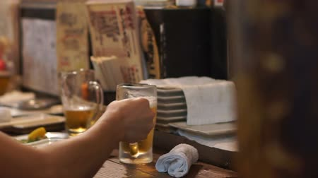 nihon : Tokyo, Japan - September 2016: Japanese bar beer izakaya restaurant. Guy drinking beer with friend at wood counter