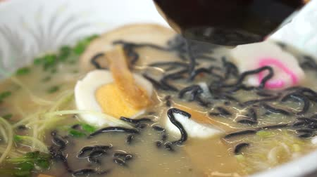 ramen : Hand eating hot Japanese ramen, black noodle with boiled egg in flavorful soup
