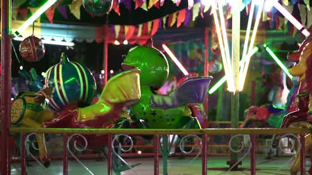 assombro : Slow motion Scary animal carousel in colorful painting. Cheap Asian carnival fair ride