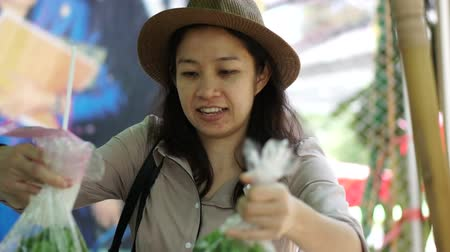 купить : Asian woman smiling wearing hat at local farmer market area. Looking and picking fresh organic vegetable
