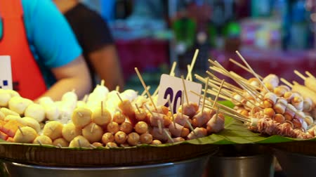 fish ball : Assorted meat ball, hot dog and sausage on skewers selling at night food market of Thailand Stock Footage