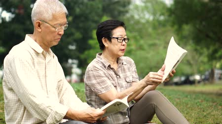 avançar : Asian senior couple reading books at the park.Spend quality time and never stop learning something new
