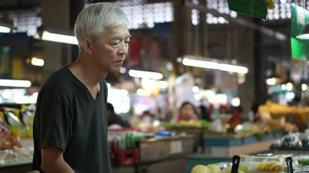 stragan : Asian senior man buying food at local market stall Wideo