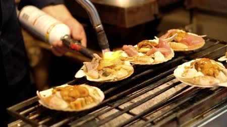 kalmar : Assorted seafood grill in shell at Tsukiji Market, Japan. Chef using burnt torch