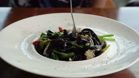 kalmar : Black squid ink pasta dish using fork to eat spaghetti