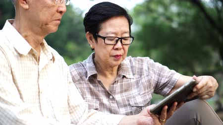 senior lifestyle : Asian senior couple using tablet together in park