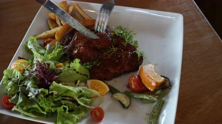 baixo teor de gordura : Hand and knife cutting short ribs bbq salad with fries 4k