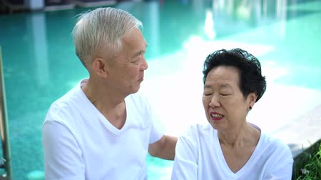тройник : Asian senior couple relax at resort, hotel pool vacation life