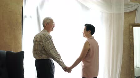 zengin : Wealthy Asian senior couple parent holding hand in front of light curtain Stok Video