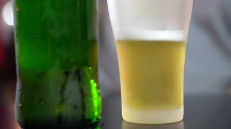 kondenzace : Frosted beer glass with golden drink inside. Green bottle close up 4K