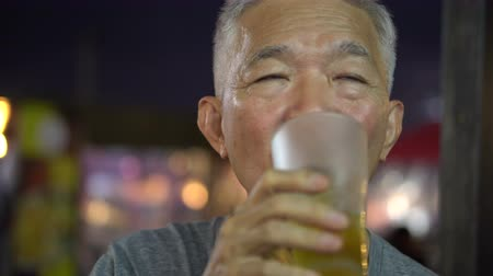 teljes test : Asian senior relax with family at outside restaurant and drink beer