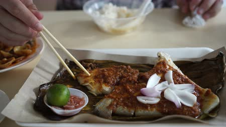 çili : Singaporean, Malaysian food grilled stingray sambal sauce serve on banana leave Stok Video
