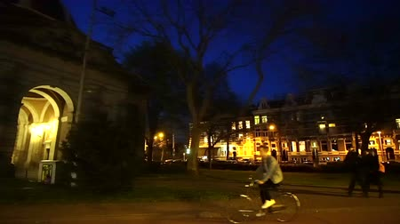 rendes : Amsterdam, Netherlands : 5 April 2017 - Night evening street view of local life in the city, apartment street and people