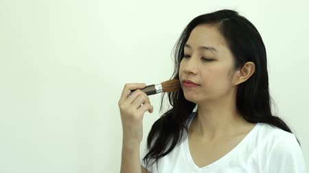 corar : Asian woman use brusher to do make up cheek brush on slow motion video
