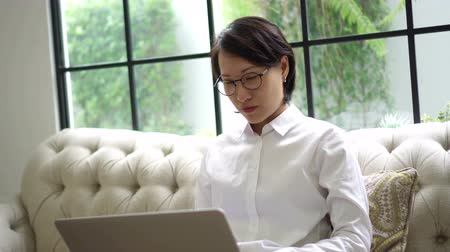 concentrar : Asian woman working at home, typing concentrate at laptop