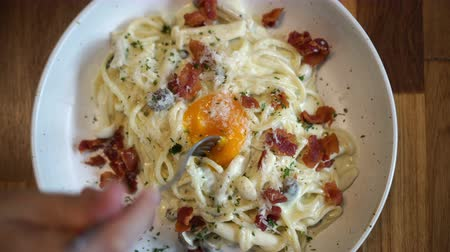 olasz konyha : Creamy avocado bacon carbonara spaghetti with egg yolk eating video Stock mozgókép