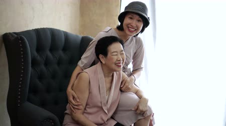 senior lifestyle : Asian mother and daughter hug, laugh have fun together at home interior background