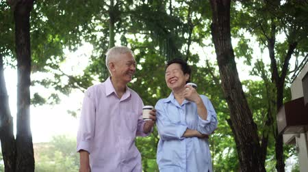 senior lifestyle : Happy Asian elderly couple morning walk in green city while drinking coffee and talking