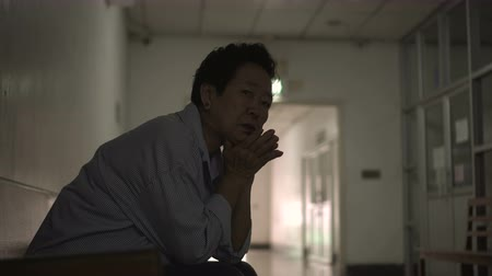 lobby : Asian senior woman waiting at hospital corridor worry and sad Stock Footage